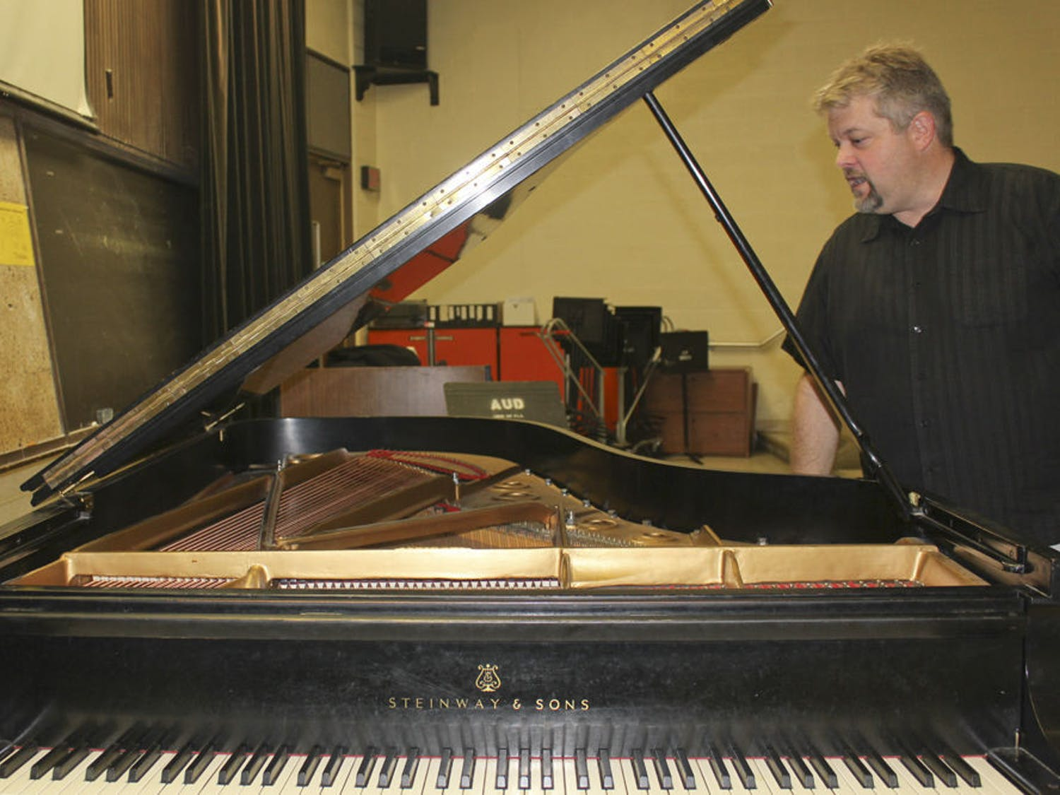 Trent Wellers, the building manager for UF's School of Music, checks whether a piano's strings are swollen to see if it needs tuning. The piano is about 70 years old.