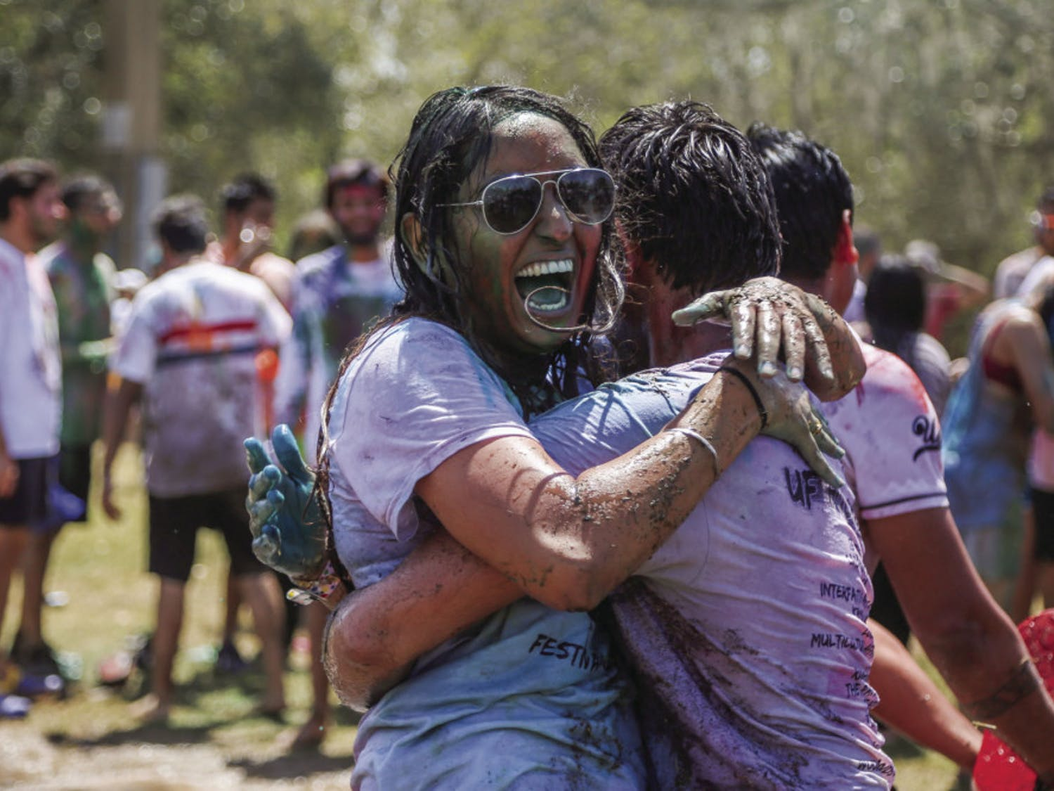 From left: Simran Giri, 19, a UF microbiology and cell science freshman who is originally from India, hugs her friend during the UF Holi Festival of Colors on Sunday afternoon. After the kickoff, many people went under water thrown by a fire truck. A mud fight followed.