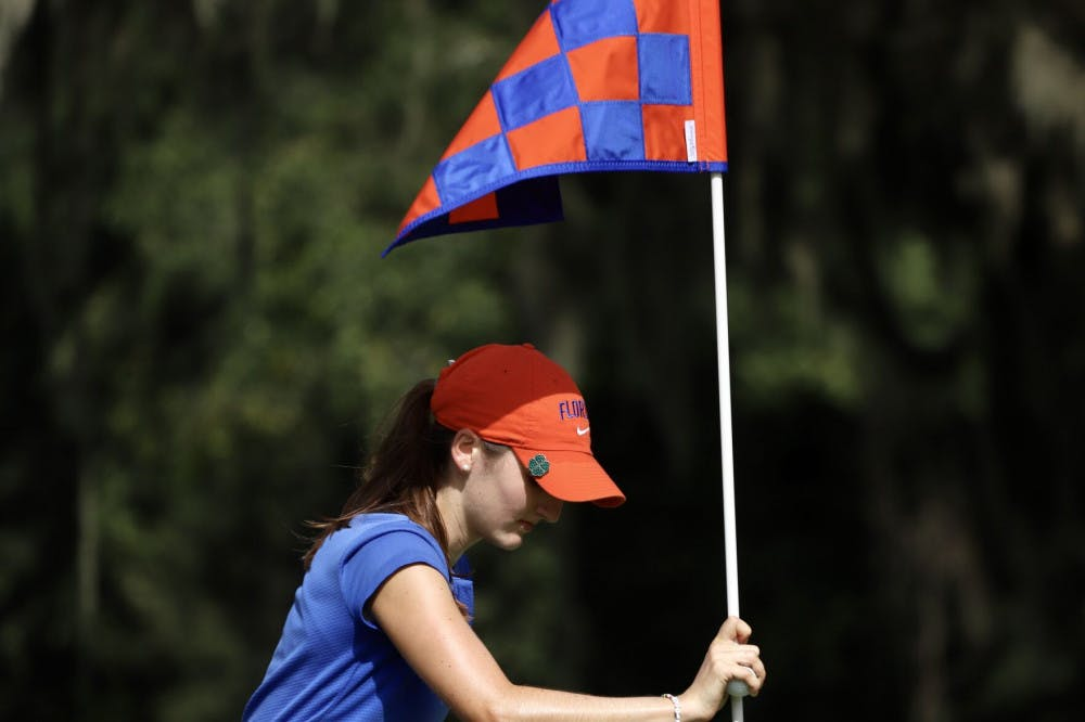 <p>Freshman Maisie Filler adjusts a flag at Mark Bostick Golf Course. She sits in a tie for 21st after shooting three over par.</p>
