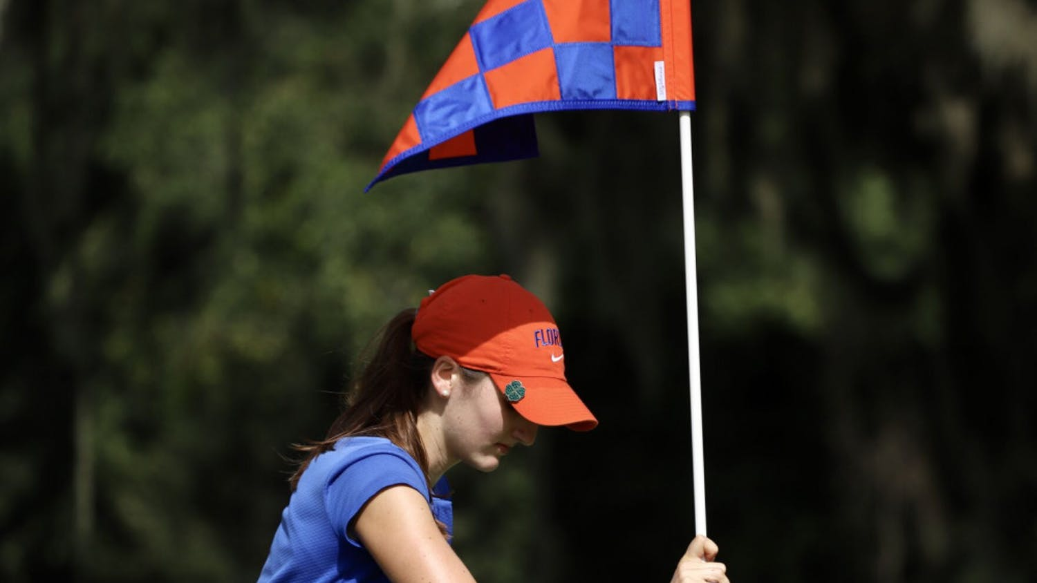 Freshman Maisie Filler adjusts a flag at Mark Bostick Golf Course. She sits in a tie for 21st after shooting three over par.