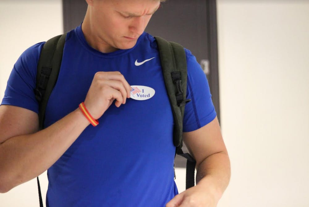 """<p><span>Nicholas Moore-Lefauve, a 20-year-old information systems and operations management major, puts on his """"I Voted"""" sticker during the first day of early voting at the J. Wayne Reitz Union Monday morning. This is the third time Moore-Lefauve has voted in his life.</span></p>"""