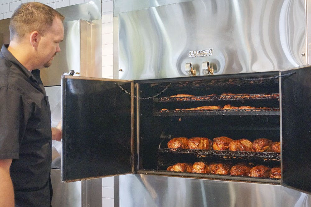 <p>Coy Joyner, assistant general manager, opens one of the barbecue smokers at Sonny's BBQ on 3635 SW Archer Road. The restaurant's new building emphasizes the oak wood smokers, putting them in full view of guests.</p>