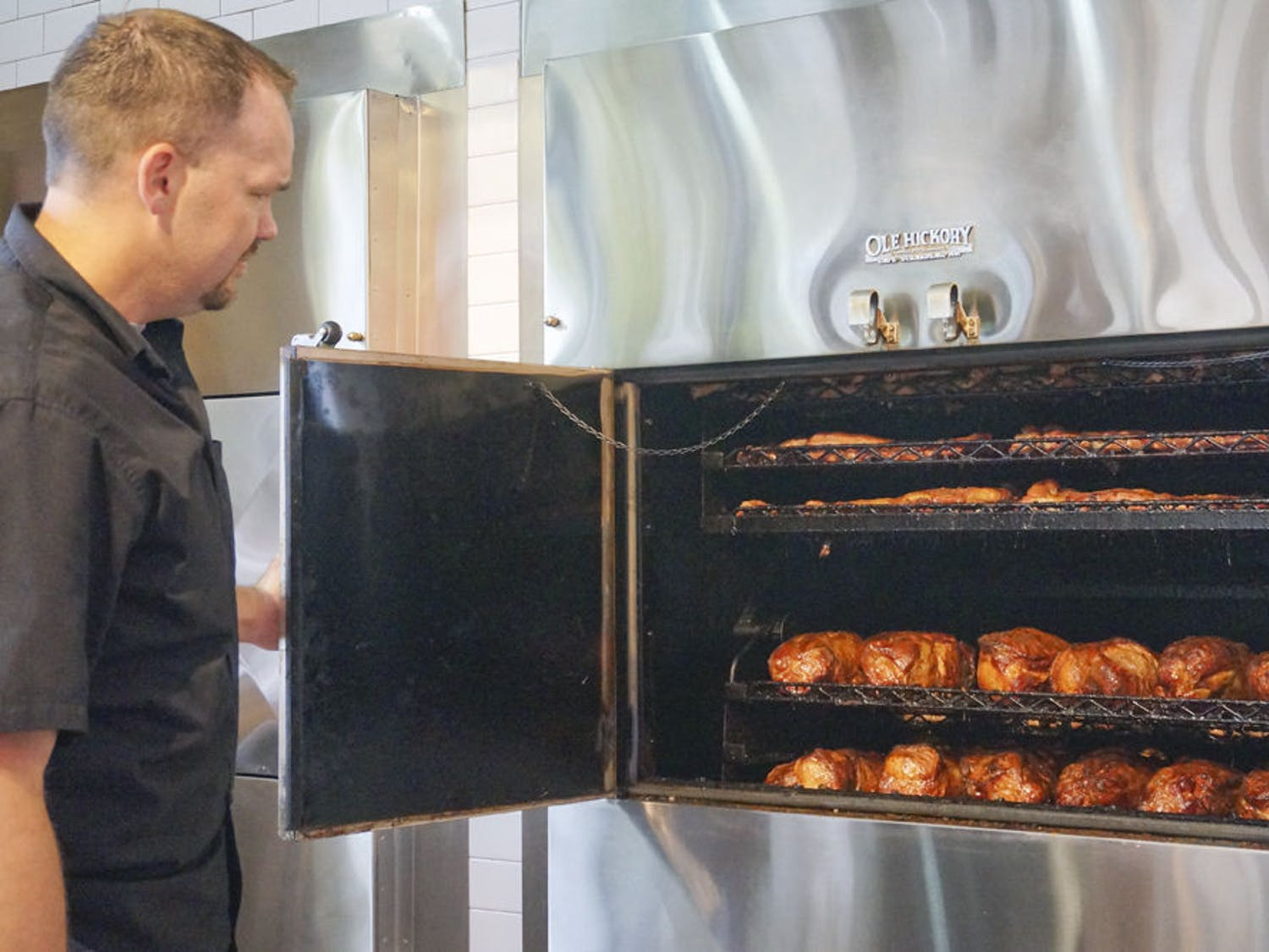 Coy Joyner, assistant general manager, opens one of the barbecue smokers at Sonny's BBQ on 3635 SW Archer Road. The restaurant's new building emphasizes the oak wood smokers, putting them in full view of guests.