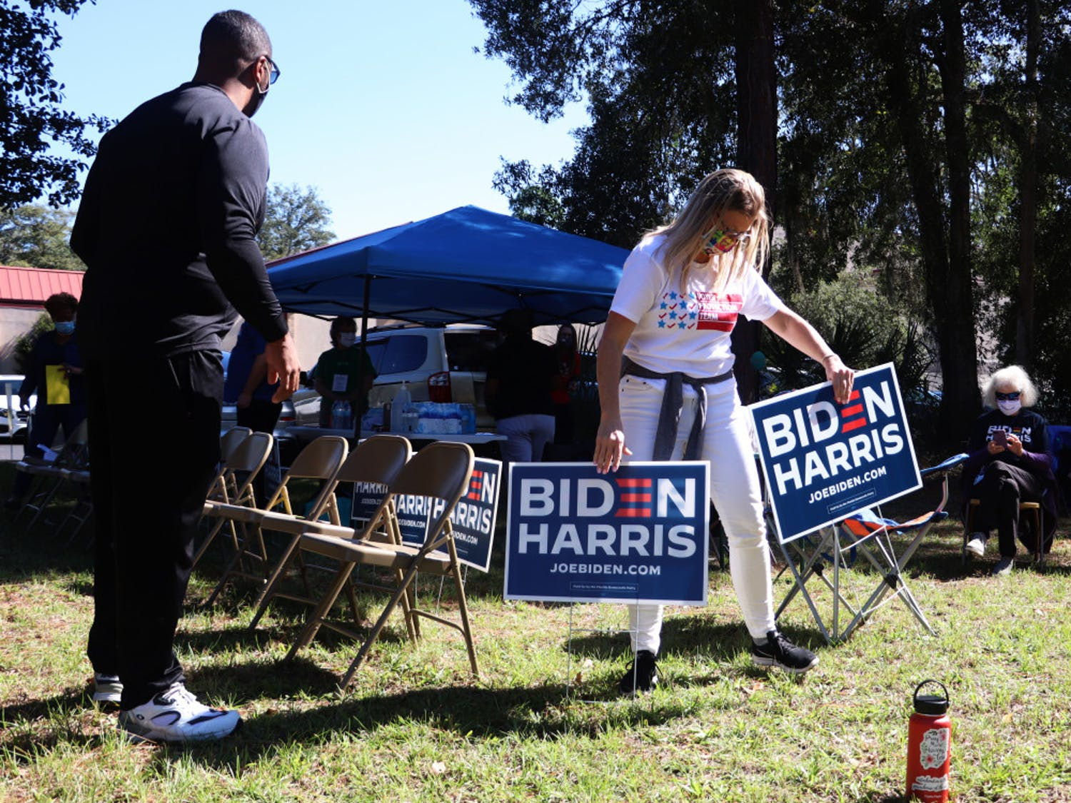 Cheree Padilla (right), a member of the Voter Protection Team, helps move the Biden campaign volunteers' signs on Tuesday, Nov. 3, 2020. The volunteers were told to move their signs and chairs to comply with the state statute that says no one can solicit voters within 150 feet of a polling location. (Lauren Witte/Alligator Staff)