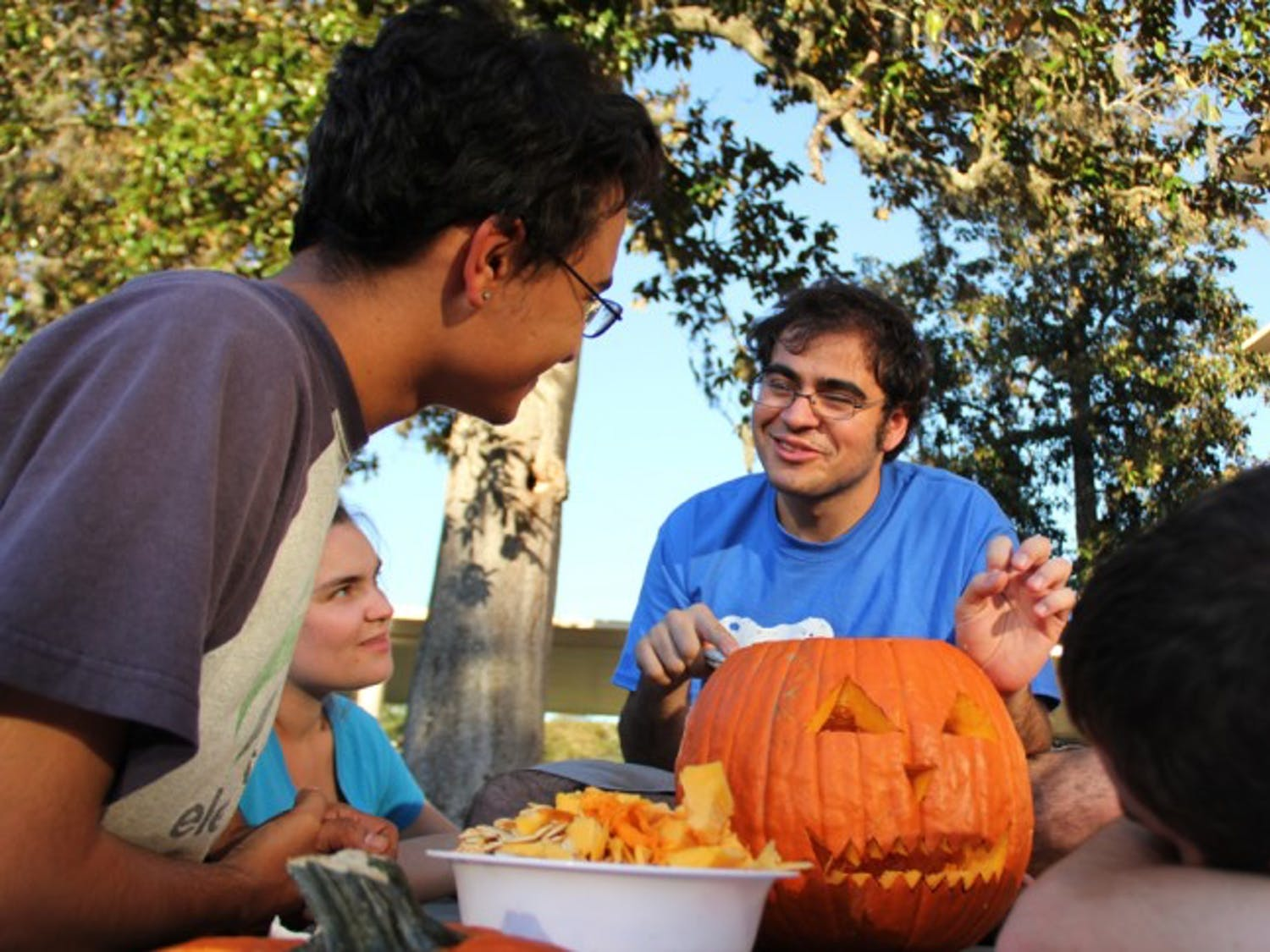 Michael Gonzalez, 20, shares his enthusiasm for carving pumpkins with his friends Ruben Quesada, 20, far left; Michelle Altemus, 20, left; and Marcus Lewis, 19, right; on Sunday afternoon.