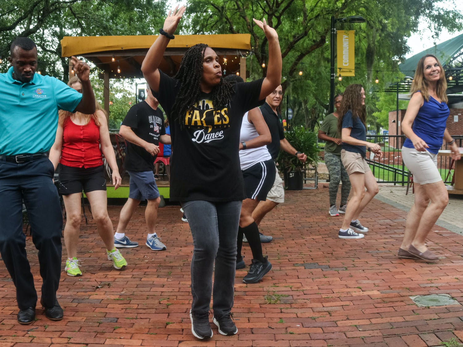 Wanda Lloyd, 47 (center), teaches students line dancing outside Muñecas Downtown Taco Garden after rain forced the class to avoid the slippery surfaces at the Bo Diddley Plaza amphitheater on Tuesday, June 22, 2021.