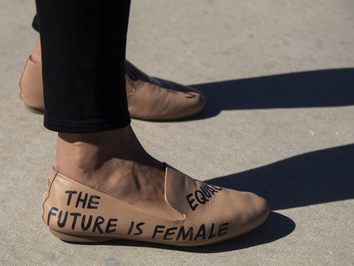 "A campaign staffer wears flats stating ""The future is female"" and ""equality"" during the ""Good Trouble"" rally held at Depot Park on Saturday, Oct. 31, 2020."