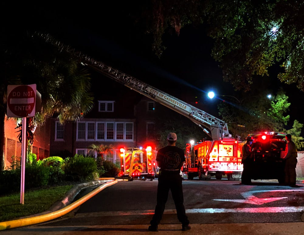 <p>An emergency responder looks on at the scene of a fire at Norman Hall Monday night.</p>