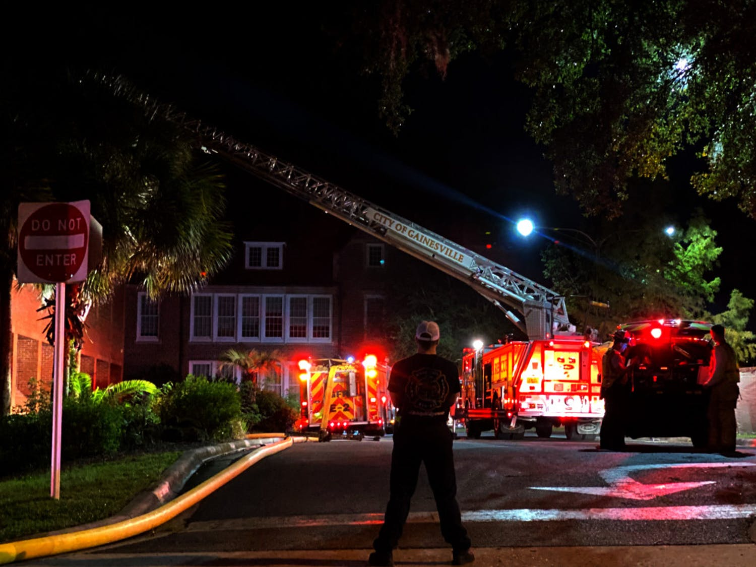 An emergency responder looks on at the scene of a fire at Norman Hall Monday night.