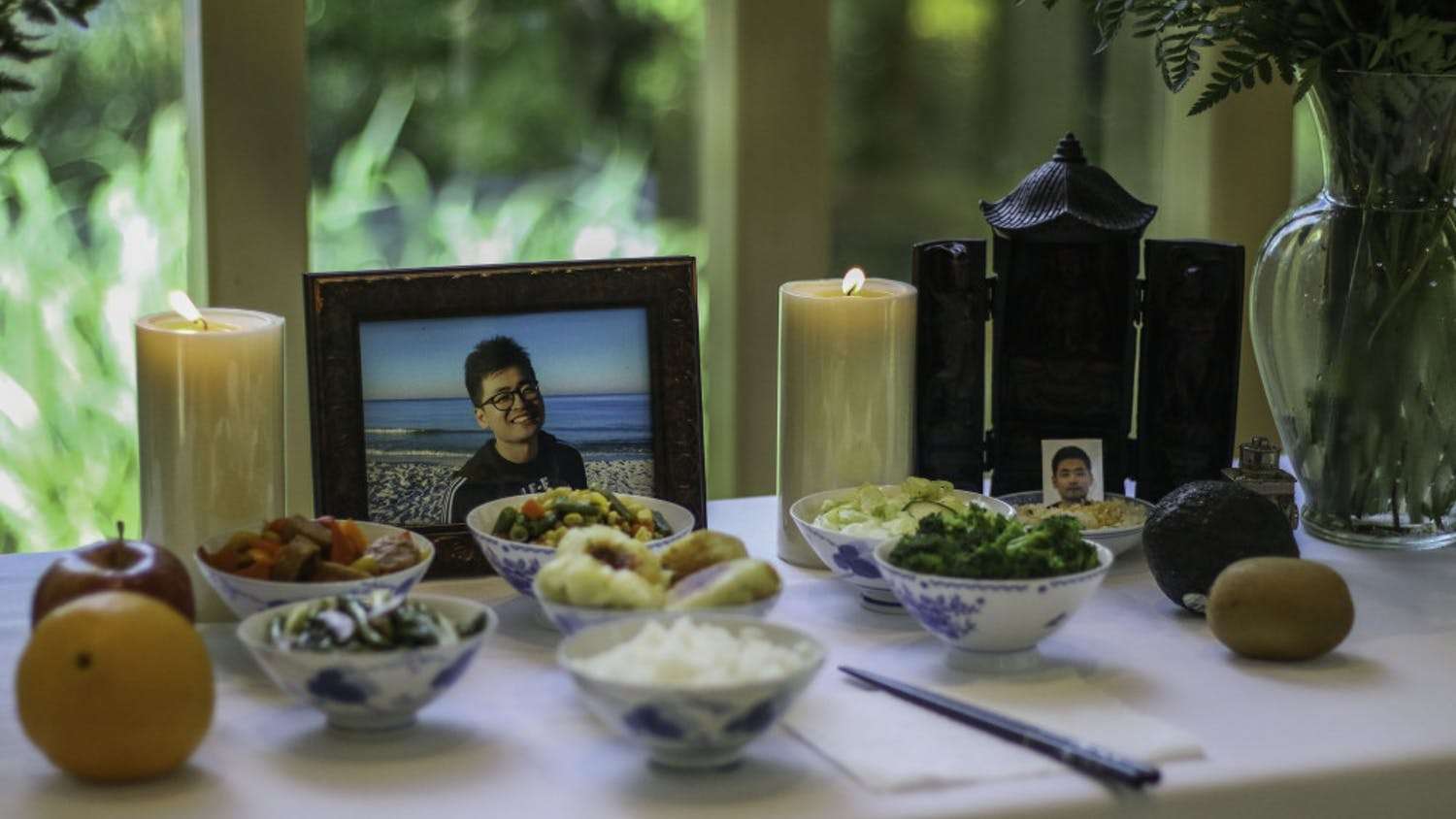 A memorial for Huixiang Chen, a University of Florida international doctoral candidate who died by suicide June 13, was made up of photos of Chen, candles and a variety of dishes Wednesday at the front of the Baughman Center during a celebration of life service. There was standing room only in the chapel as over 150 people gathered to remember Chen and pay respects to the family.