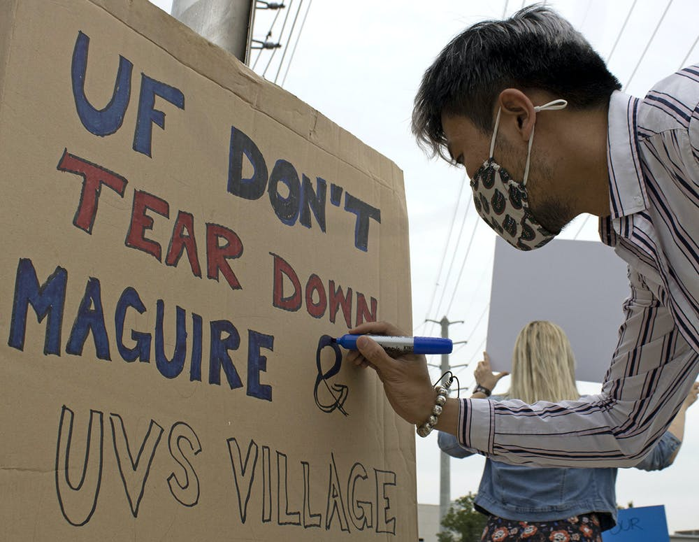 "Edward Ke Sun, 30, a PhD candidate for architectural history, theory and criticism at UF, colors a sign that reads ""UF Don't Tear Down Maguire & UVS Village"" on Friday, April 9, 2021. Sun protesting to raise awareness about UF's plan to demolish three out of the five graduate student housing complexes in Gainesville."