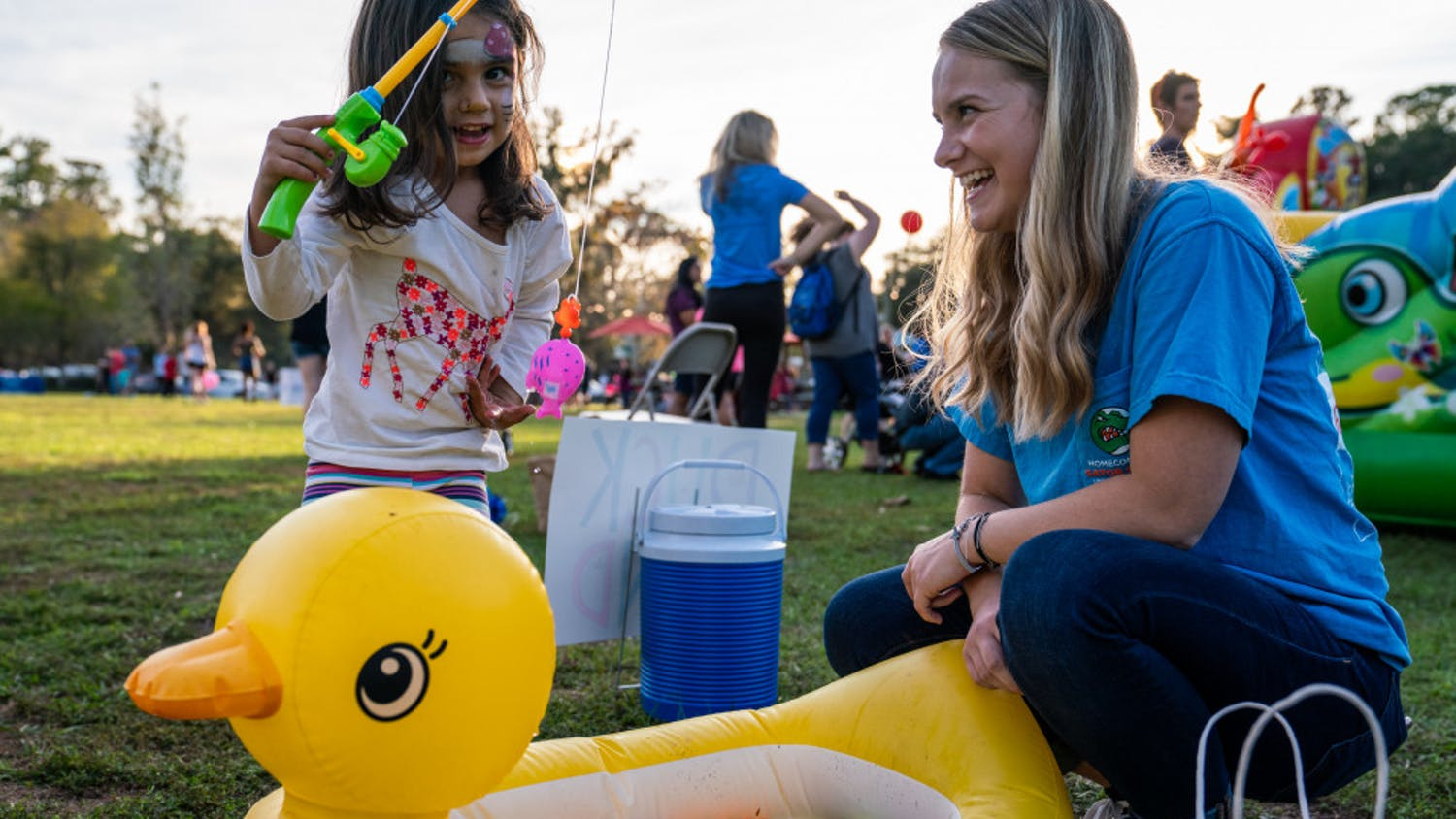 """Volunteer Drew McCullough, 18, laughs as she watches a child fish for prizes during Sunday's """"Hey, Neighbor!"""" carnival held at Magnolia Parke Square. McCullough, a UF sociology freshman, was recently diagnosed with Type 1 diabetes and received support from the UF Diabetes Institute's support group. The institute, along with UF's College Diabetes Network chapter, hosted the event to celebrate National Diabetes Awareness Month."""