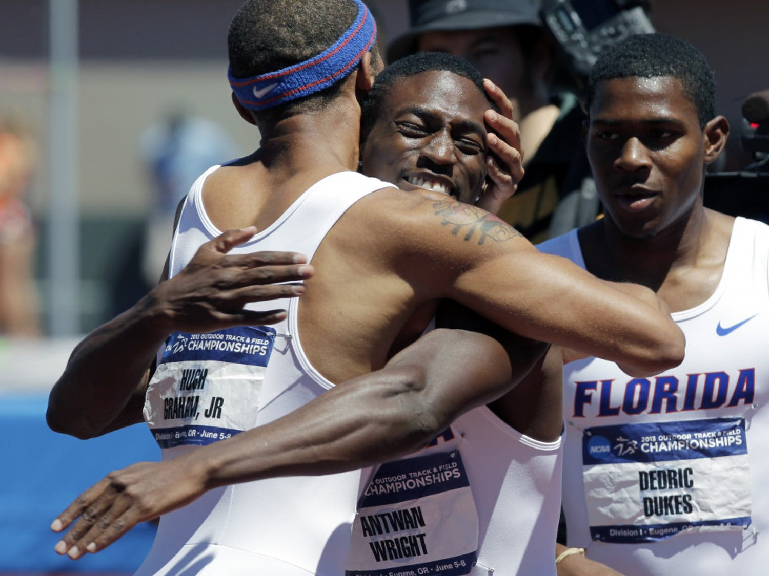 Florida's Hugh Graham Jr., left, hugs Antwan Wright as teammate Dedric Dukes looks on after winning the 4x400-meter race during the NCAA outdoor track and field championships in Eugene, Ore., Saturday, June 8, 2013. Florida tied with Texas A&M for the men's championship.
