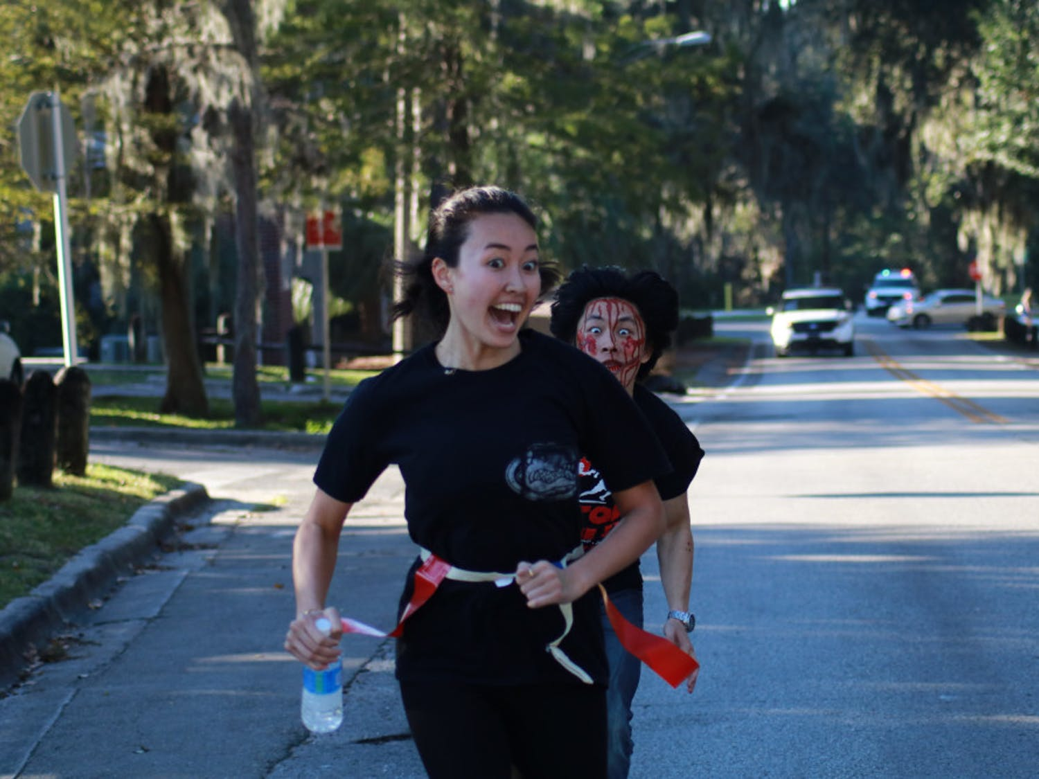 Leeson Chen, a 21-year-old UF computer science sophomore, chases Isabelle Lady, a 20-year-old UF biology junior, as she finishes the last leg of the Gator Zombie 5K. Participants wore flag football belts as they ran while volunteer zombies chased them and tried to pull them off.