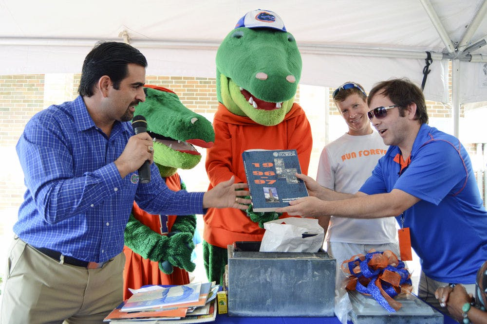 <p>Tony Medina (left), president of the UF Association of Hispanic Alumni, announces Saturday morning the contents of a time capsule buried in 1996 by the UF Class of 1995. Bruce Floyd (far right), social media manager for the University of Florida Athletic Association and member of the Class of 1995, holds a copy of the 1996-1997 undergraduate catalogue, while Dan Clarke, 43, also a member of the Class of 1995, looks on.</p>