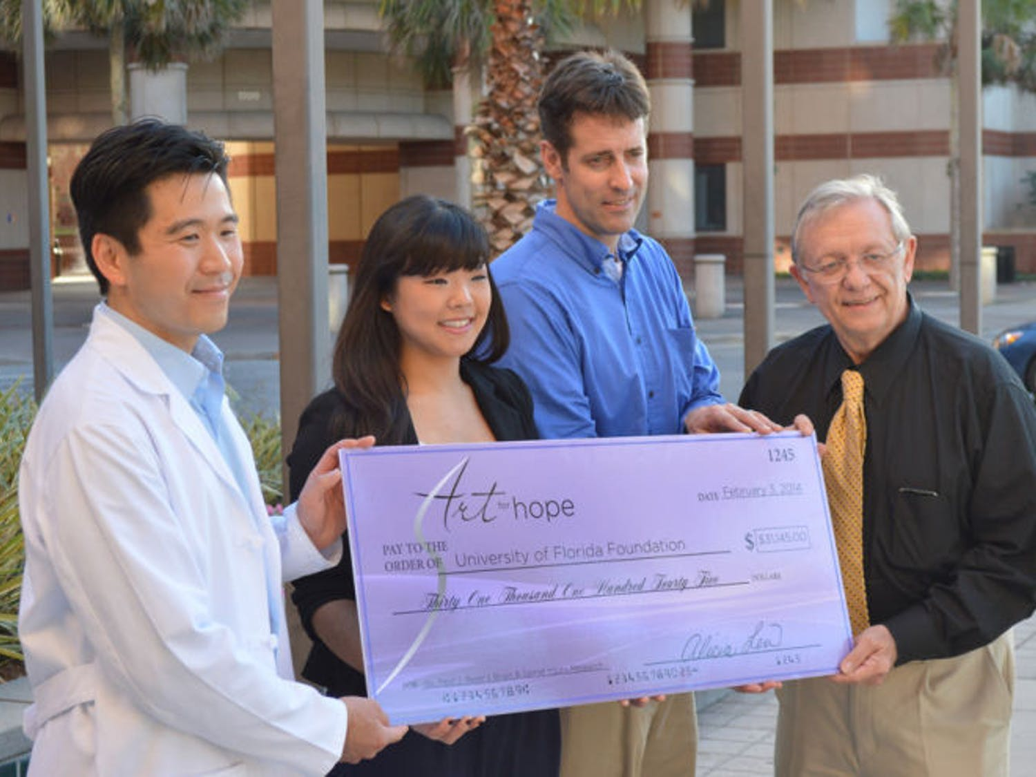 Alicia Lew presents a check on Monday afternoon at the McKnight Brain Institute to Paul J. Reier, who said he wants to buy new equipment.