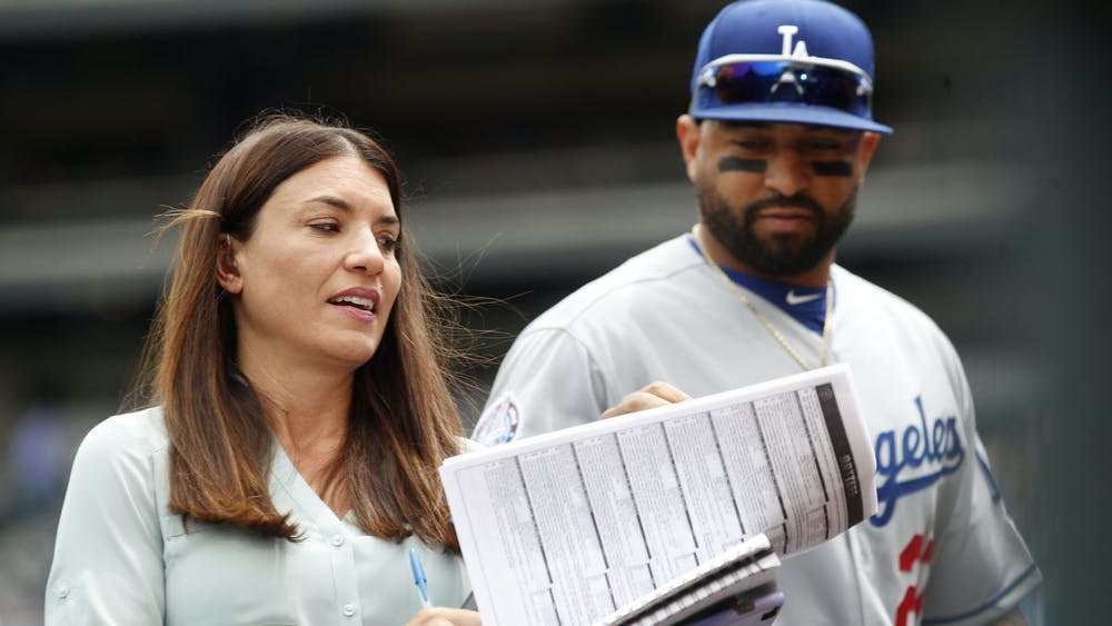 Alanna Rizzo, left, delivers a report before a 2018 game between the Los Angeles Dodgers and Colorado Rockies in Denver as then-Dodgers left fielder Matt Kemp looks on. Rizzo on Tuesday night will be part of Major League Baseball's first all-female broadcasting crew. [ DAVID ZALUBOWSKI   AP ]