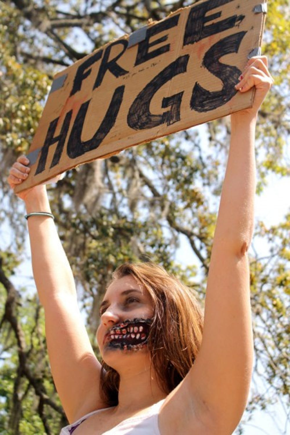 """<p>Eighteen-year-old animal biology freshman Megan Smith, dressed as a zombie, offers """"free hugs"""" to passersby in Turlington on Tuesday to promote the Humans vs. Zombies game.</p>"""