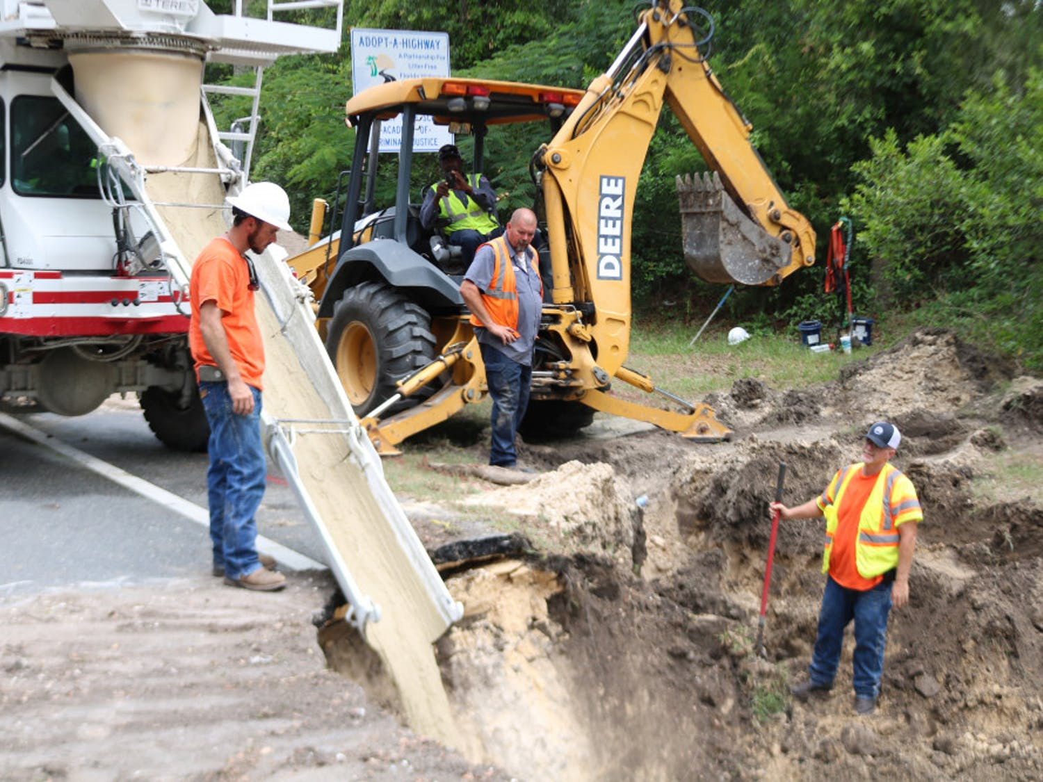 Construction workers from Newberry utilities pour concrete to fill a 20-foot deep sinkhole that opened on West Newberry Road on Wednesday morning.