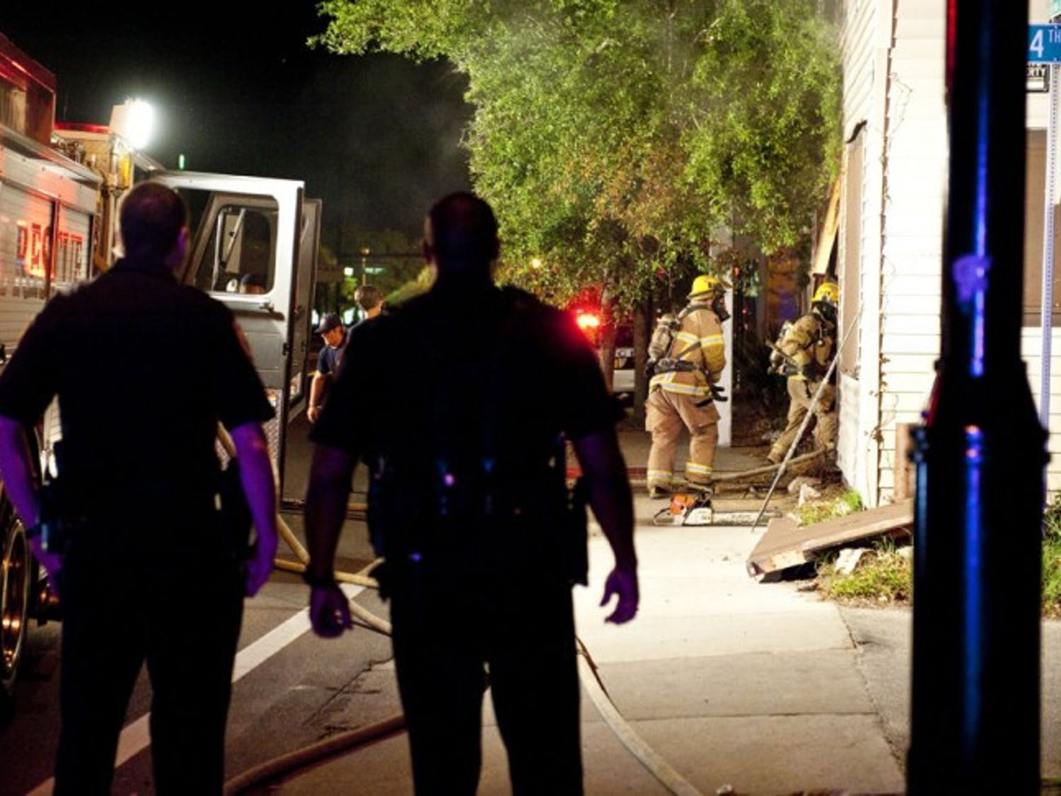 Gainesville Police officers look on as Gainesville Fire Rescue workers enter a building on Northwest 13th Street late Tuesday night.