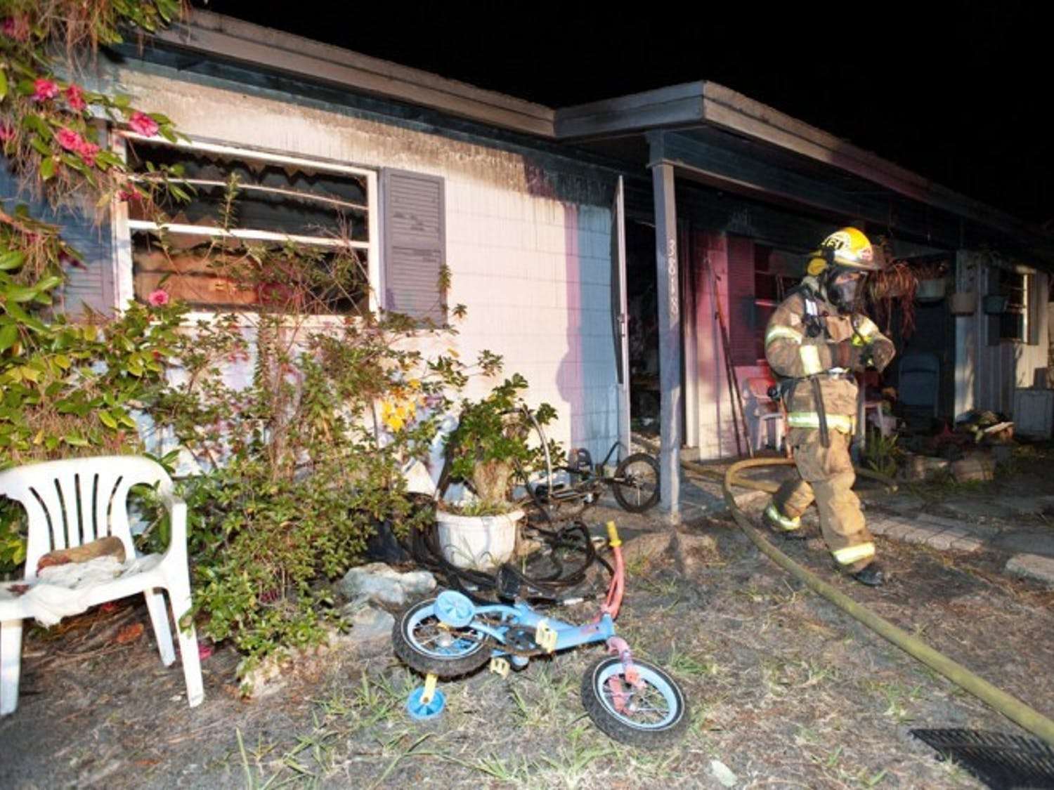 A firefighter walks out of a burned house at 3818 NE 12th St. Fire Rescue District Chief Richard Saulsberry said five adults and two children lived in the house, but only one elderly woman was home at the time of the incident.