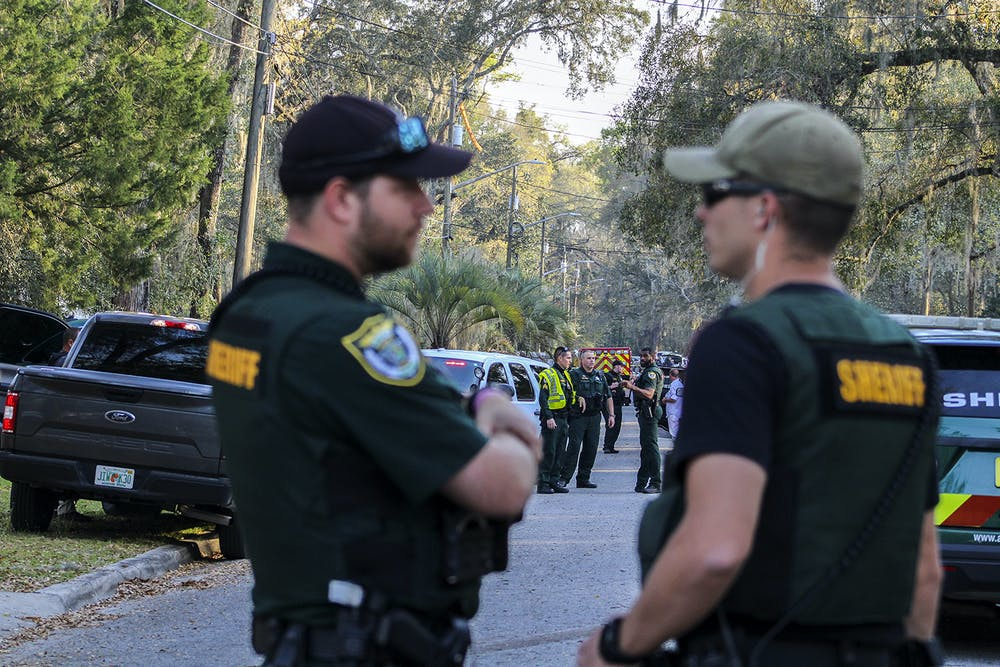 <p>Law enforcement from the Alachua County Sheriff&#x27;s Office stand near crime scene tape on Southeast 46th Terrace on Friday, March 5, 2021, where a person died after a shootout between ACSO deputies and the individual.</p>
