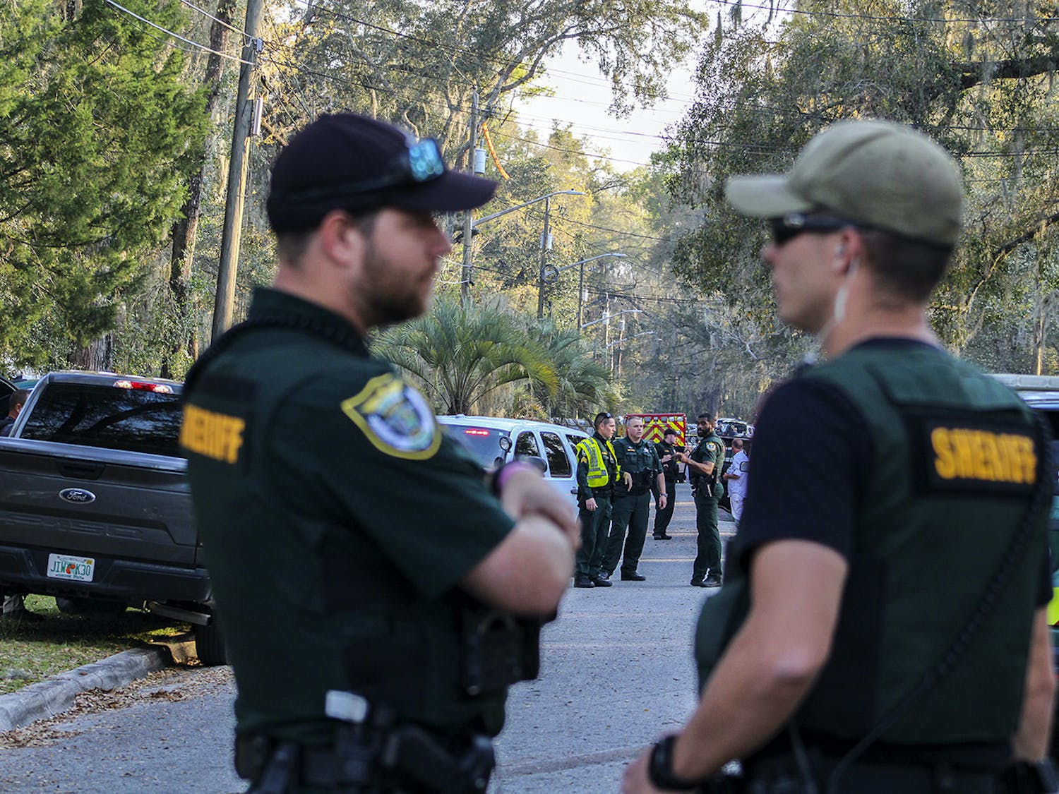 Law enforcement from the Alachua County Sheriff's Office stand near crime scene tape on Southeast 46th Terrace on Friday, March 5, 2021, where a person died after a shootout between ACSO deputies and the individual.