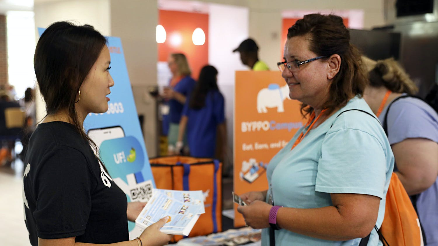 BYPPOCAMPUS founder and CEO Victoria Liu, (left) a UF accounting alumna, introduces her food delivery business to Stephanie Landini, (right) a parent of a UF student, at Gator Dining Center in Gainesville on Friday, July 9, 2021.