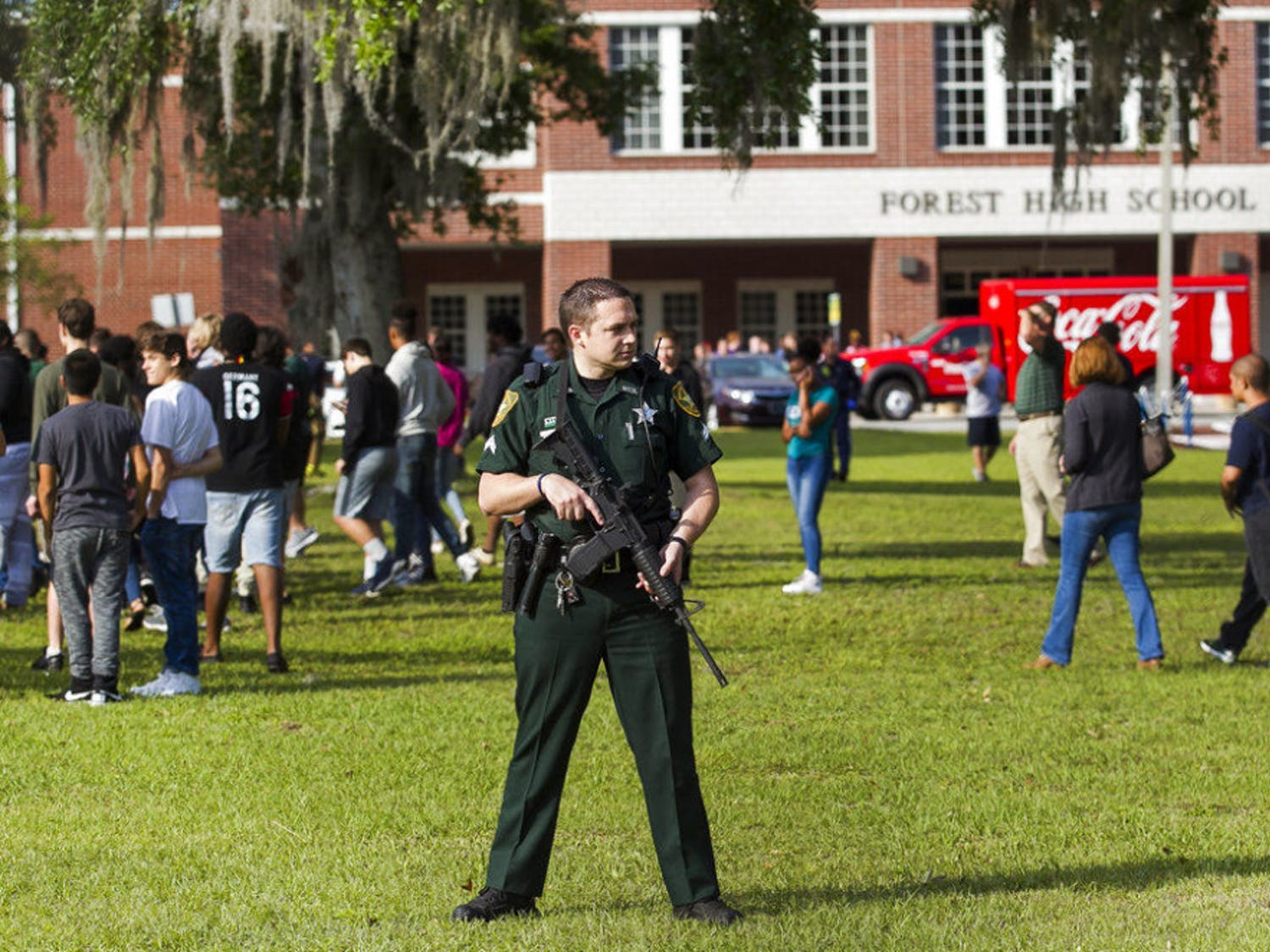 A Marion County Sheriff's Deputy stands outside Forest High School as students exit the school after a school shooting occurred, Friday, April 20, 2018 in Ocala, Fla. One student shot another in the ankle at the high school and a suspect is in custody, authorities said Friday. The injured student was taken to a local hospital for treatment. (