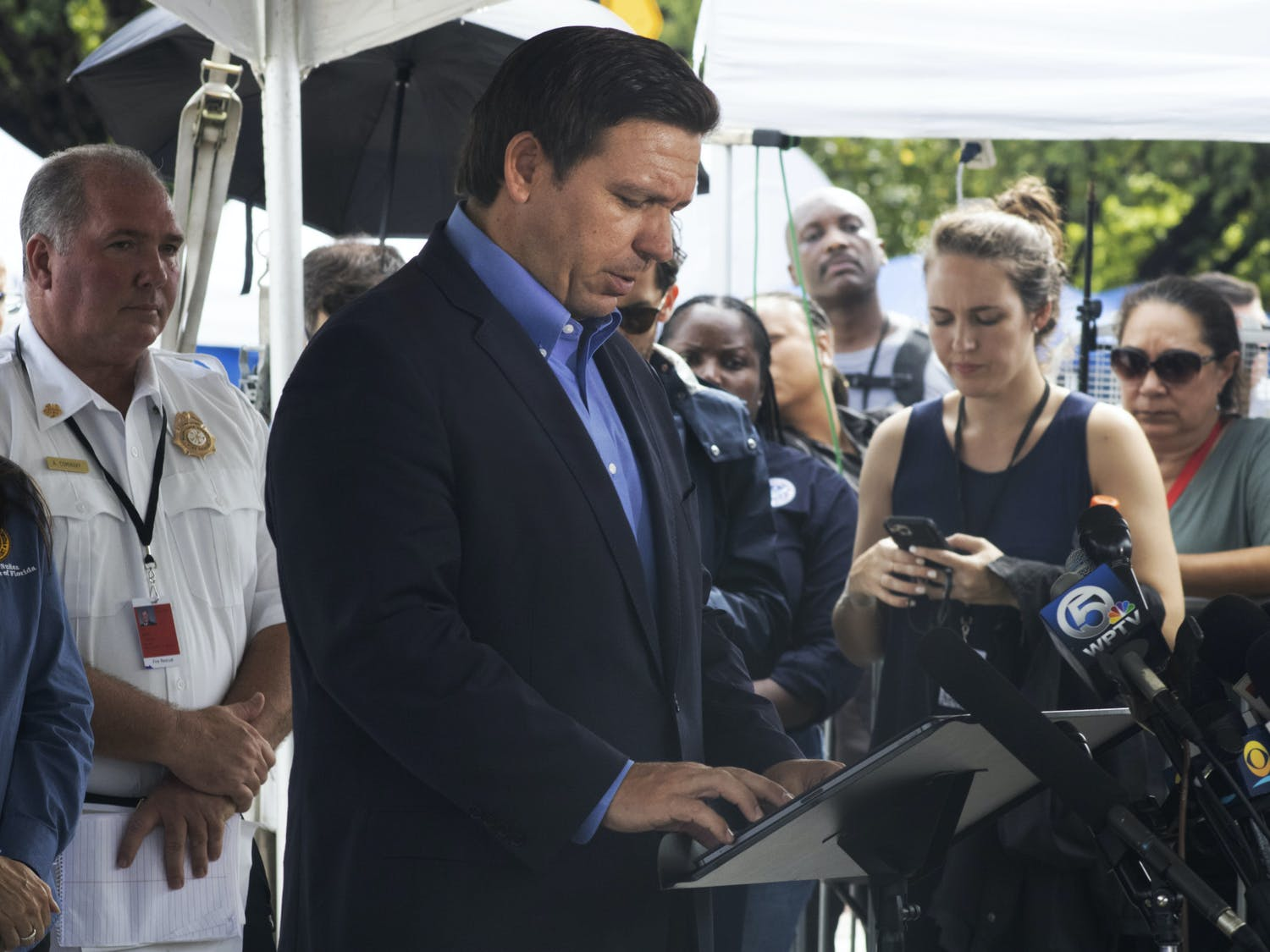 Gov. Ron DeSantis looks down at his notes as he speaks to a crowd of reporters in Surfside, Florida on Thursday, July 1, 2021.