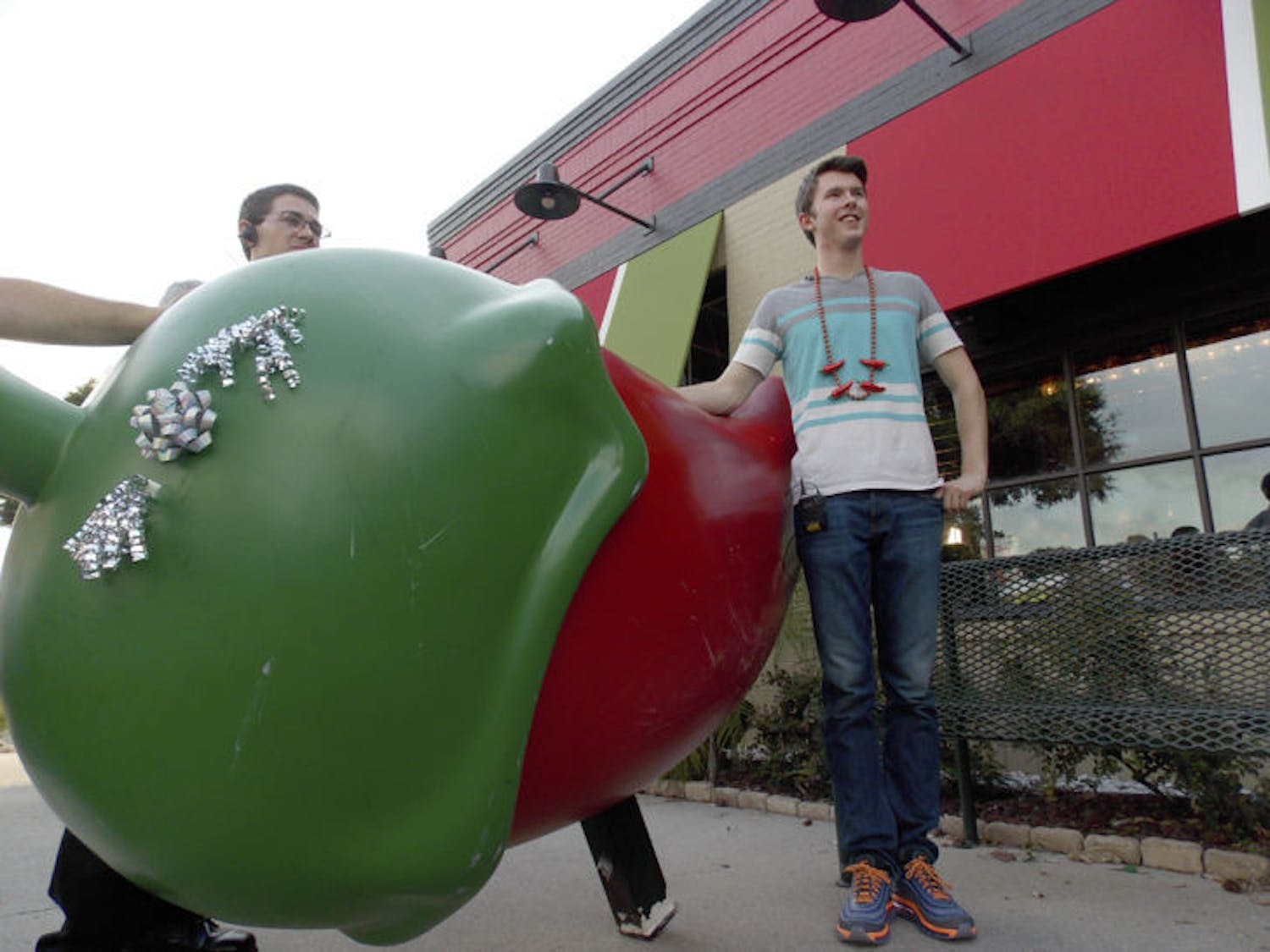 Daniel Helfrich, a 19-year-old UF classics junior, stands in front of his replacement pepper as Chili's representatives watch the occasion. His former chili was stolen.