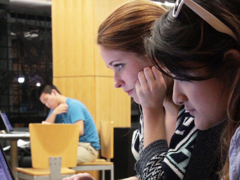 UF advertising juniors Katy Whitehurst, 20, and Ria Burgos, 20, study at Library West on Sunday night.