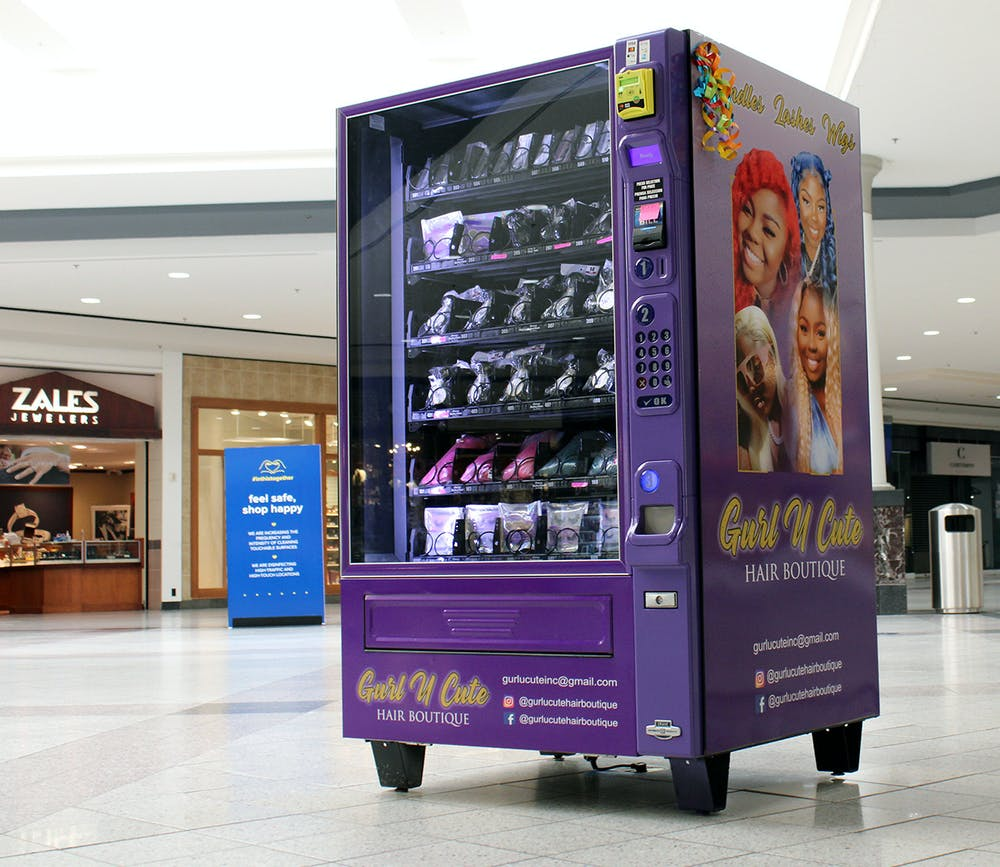 A purple vending machine owned by the Gurl U Cute Hair Boutique sits near the entrance of Oaks Mall in Gainesville on Thursday, Feb. 18, 2021. The vending machine has wig bundles and false lashes for purchase.
