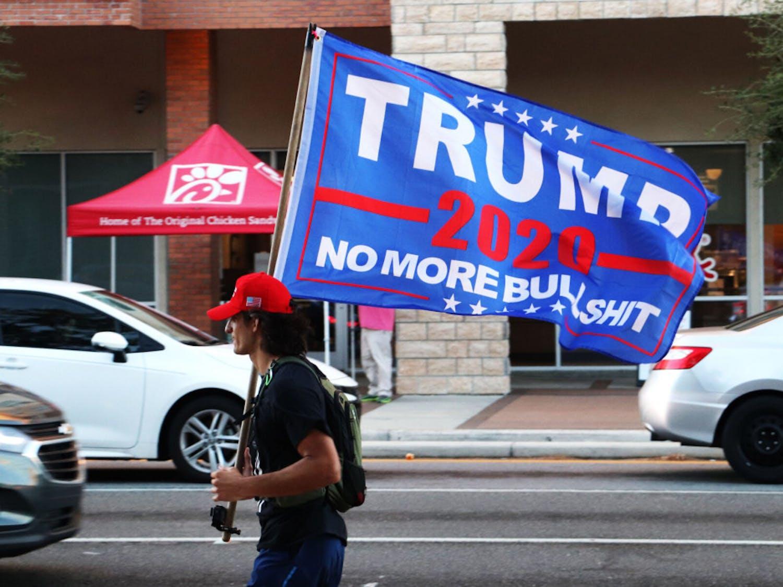 "Austin H., 22, runs on the sidewalk on W. University Avenue with a ""Trump 2020"" flag on Tuesday, Nov. 3, 2020. (Lauren Witte/Alligator Staff)"