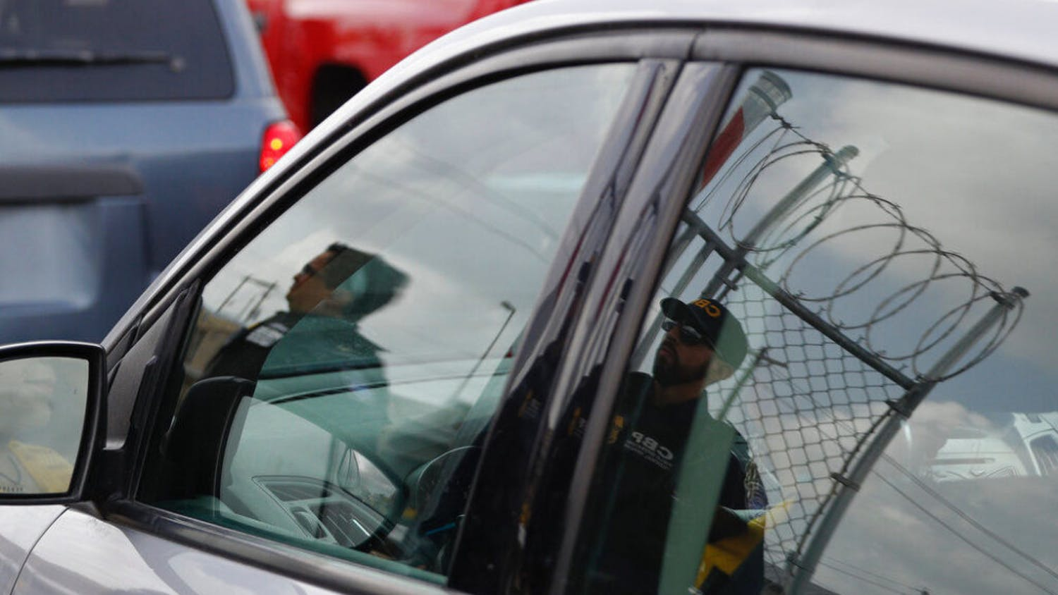 Customs and Border Protection agents are reflected in the window of an entering car, as they survey vehicles entering the U.S. on the Puerta Mexico international bridge leading into Brownsville, Texas from Matamoros, Mexico, Friday, June 28, 2019. Hundreds of migrants from Central America, South America, the Caribbean and Africa have been waiting for their number to be called at the bridge in downtown Matamoros, to have the opportunity to request asylum in the U.S.