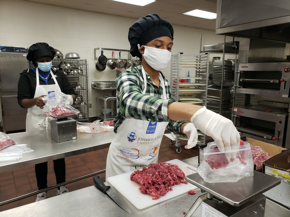 <p>Eastside High students Khyeisha Boykins and Jay&#x27;Marlon Wilson prepare food for eligible families [Photo courtesy of Alachua County Public Schools Spokesperson Jackie Johnson]. </p>