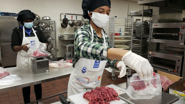 Eastside High students Khyeisha Boykins and Jay'Marlon Wilson prepare food for eligible families [Photo courtesy of Alachua County Public Schools Spokesperson Jackie Johnson].