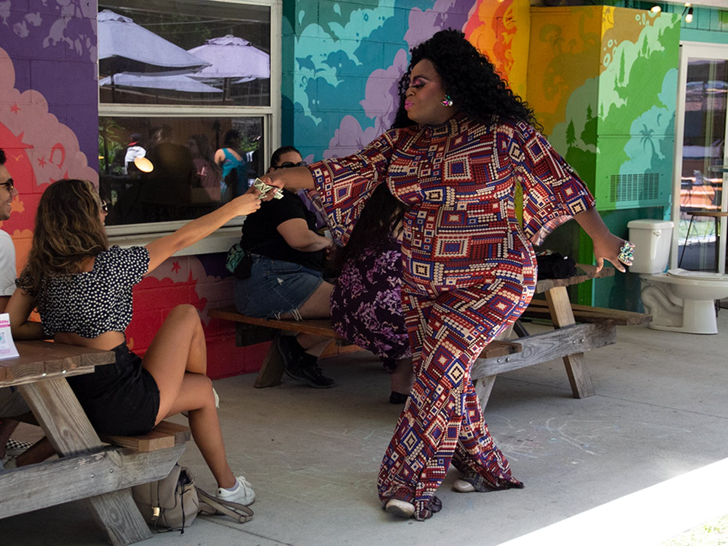 Drag Queen performer Ceazia Giovanni Kreshé gets tipped for her dance moves.