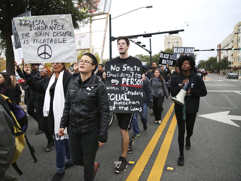 Protestors for the #BLACKLIVESMATTER march walk west on University Avenue Monday afternoon.