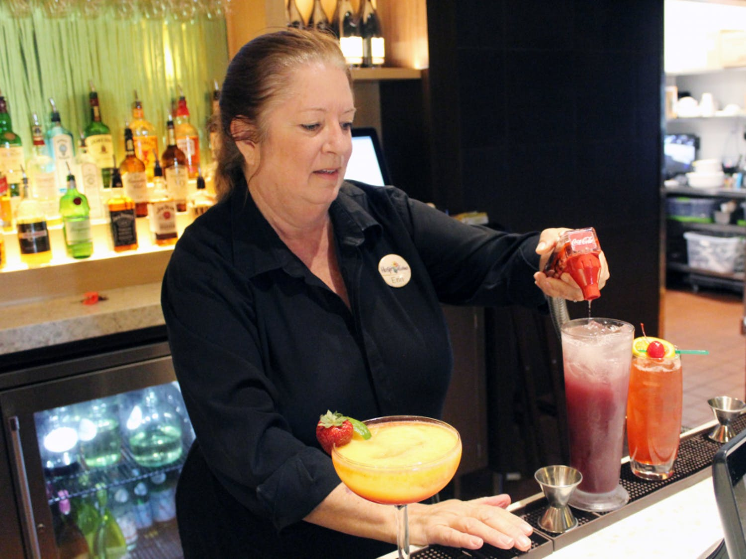 Erin Gosselin tops off a drink with Coca-Cola before handing it to a server Thursday. Gosselin is a bartender at the Olive Garden Italian Restaurant on Clark Butler Boulevard.
