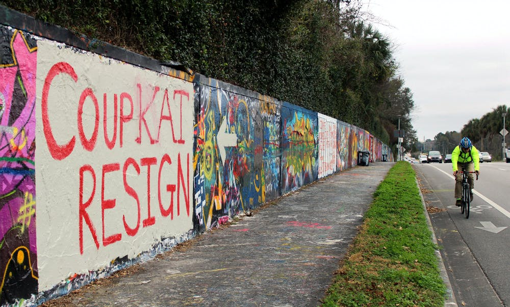 """A cyclist and cars pass by a mural on a wall along Northwest 34th Street that reads """"Coup Kat Resign"""" in Gainesville, Tuesday, Jan. 12, 2021. The mural refers to the newly elected U.S Representative Kat Cammack."""