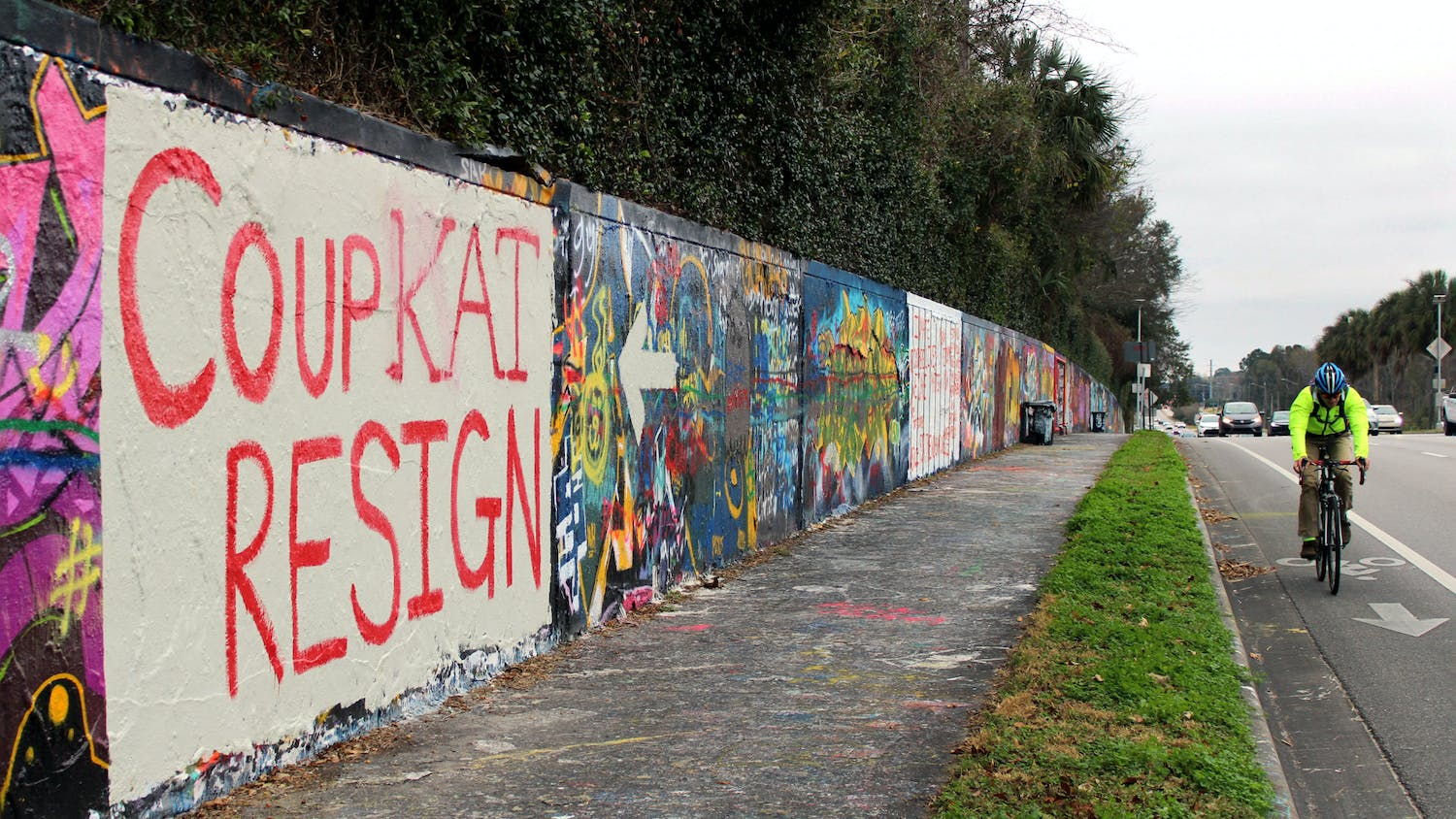 "A cyclist and cars pass by a mural on a wall along Northwest 34th Street that reads ""Coup Kat Resign"" in Gainesville, Tuesday, Jan. 12, 2021. The mural refers to the newly elected U.S Representative Kat Cammack."