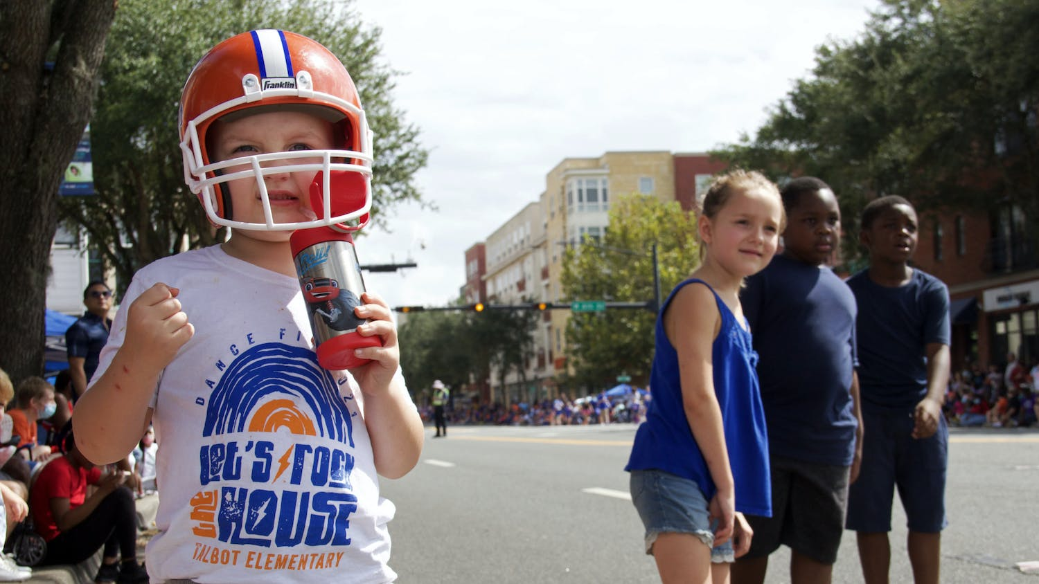 Gavin Hughes (left), Haddie Hughes (middle), and twins Emanuel and Elijah Harmon (right) watch the UF Homecoming Parade approach on University Avenue on Friday, Oct. 8, 2021.