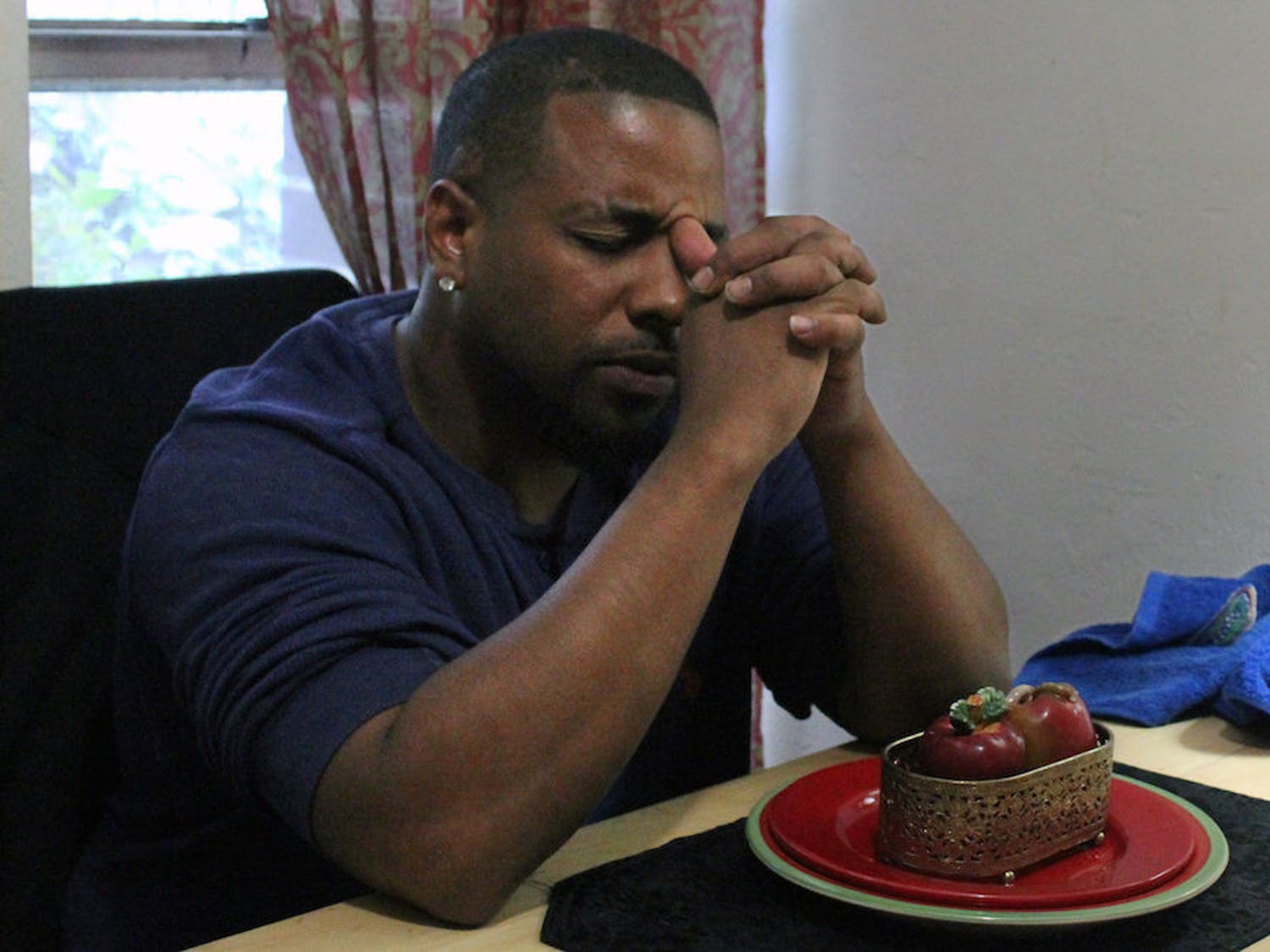 Michael Powers, 31, sits at his dining table where he is about to eat a baked chicken dinner for himself and his three sons. He lives in East Gainesville public housing, but dreams of moving to Savannah, Georgia.