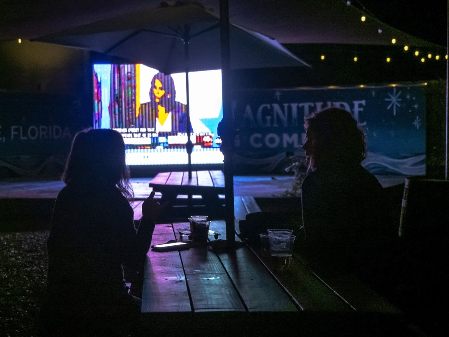Two women watch the presidential election results at First Magnitude Brewery, located in Gainesville, Fla., on Tuesday, Nov. 3, 2020. (Emily Felts/Alligator Staff)