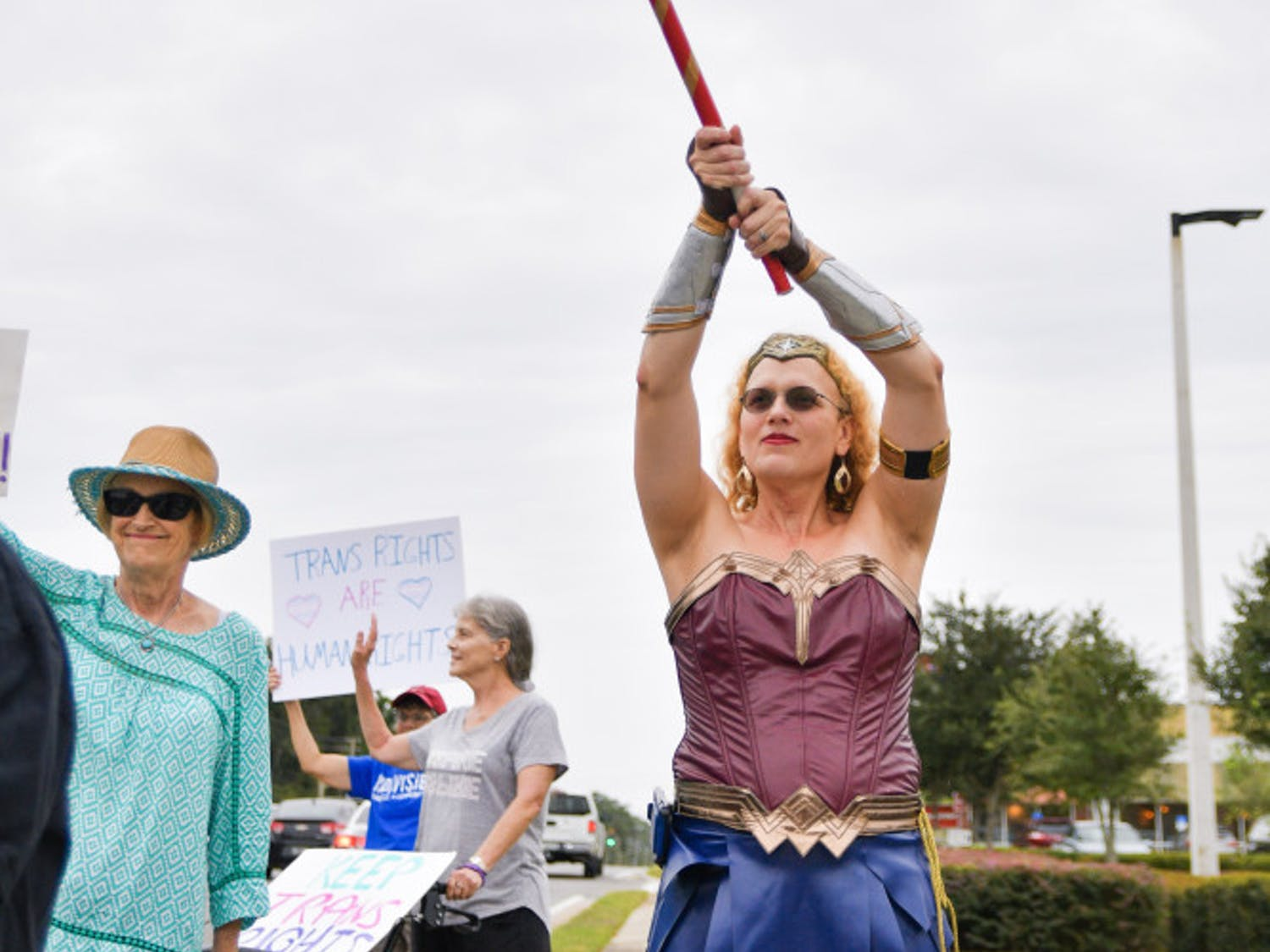 """Melina Rayna Svanhild Farley-Barratt, a 39-year-old Gainesville activist, waves a transgender flag during the """"Won't Be Erased!"""" rally Tuesday afternoon. The Trans Rights Action Committee hosted the event outside Hobby Lobby as a response to President Trump's statement recently about eliminating the status of transgender and having a person's sex be determined at birth. The Hobby Lobby was chosen as the location due to its public stance against the LGBTQ+ community."""