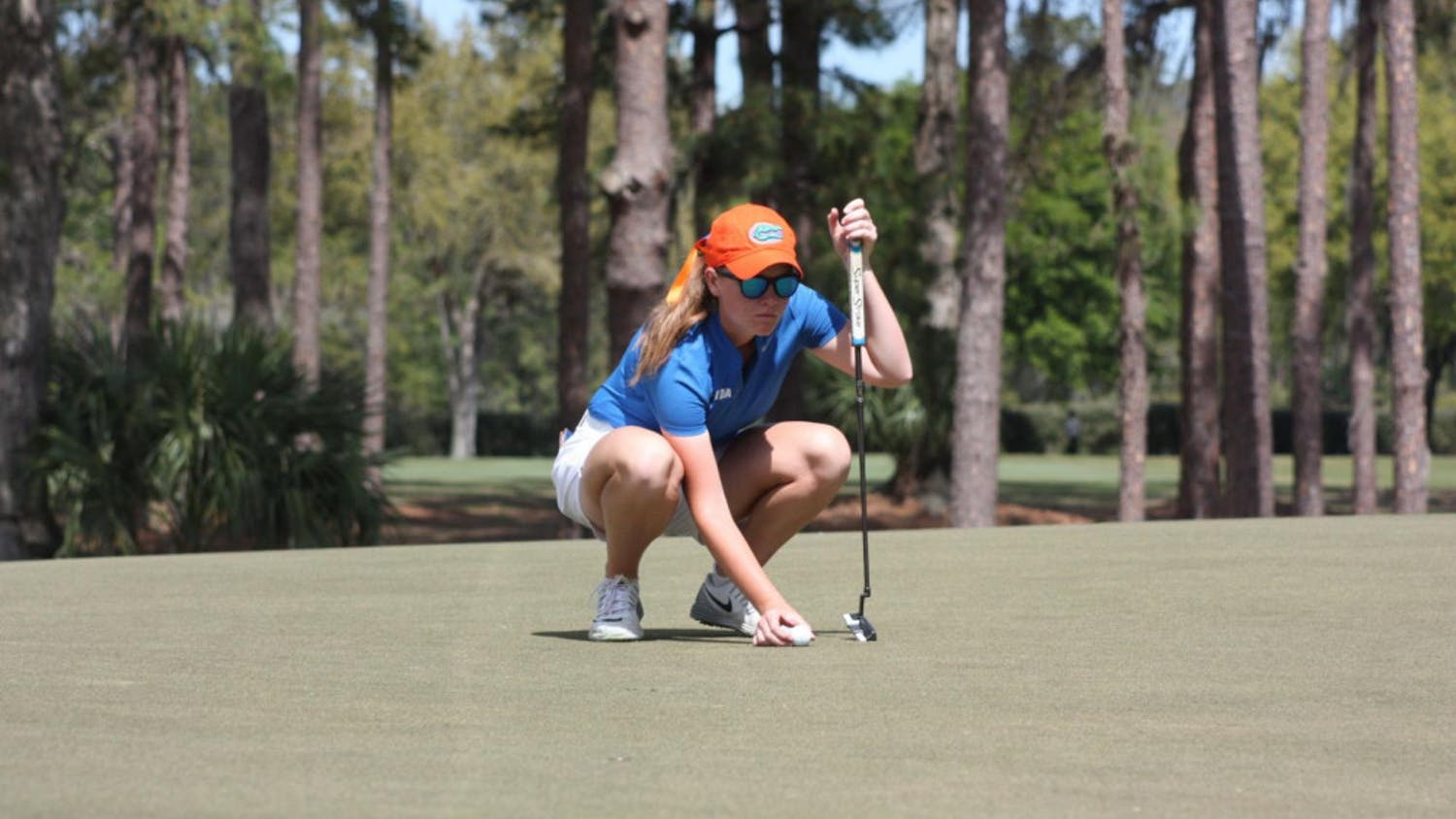 Junior Addie Baggarly kneels down to contemplate a putt. She shot an even par on Monday, currently sitting 39th in the Moon Golf Invitational heading into the final day