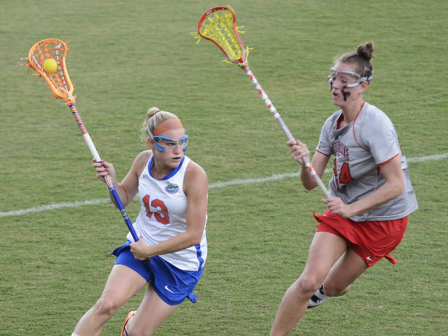 Florida attacker Ashley Bruns (13) runs past Ohio State defender Tayler Kuzma (24) in the Gators' 13-7 win against the Buckeyes on March 23 at Dizney Stadium. Bruns scored four goals in Florida's 16-5 win against Denver in the second round of the NCAA Tournament.