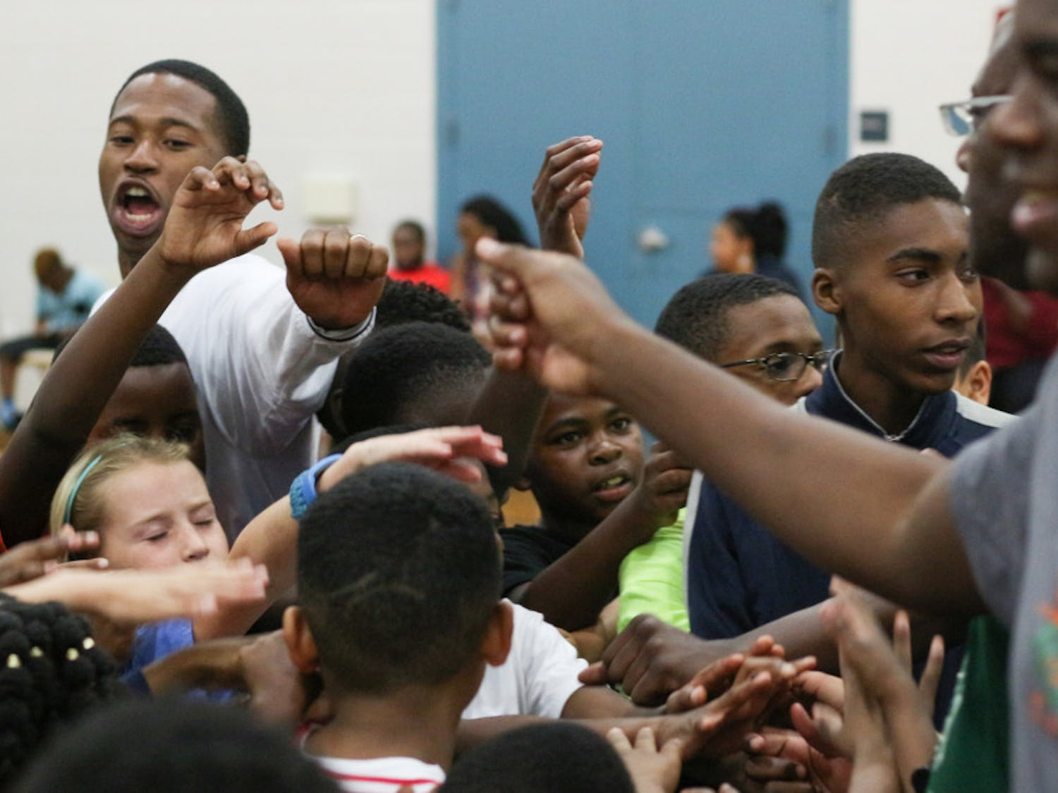 """From left: Ron Larris, a 30-year-old trainer at Nigie Hoops and former Gainesville High School basketball player, cheers """"Team!"""" with 46 kids and some Eastside High School basketball coaches during a free basketball clinic held at the Martin Luther King Jr. Multipurpose Center on Monday night."""