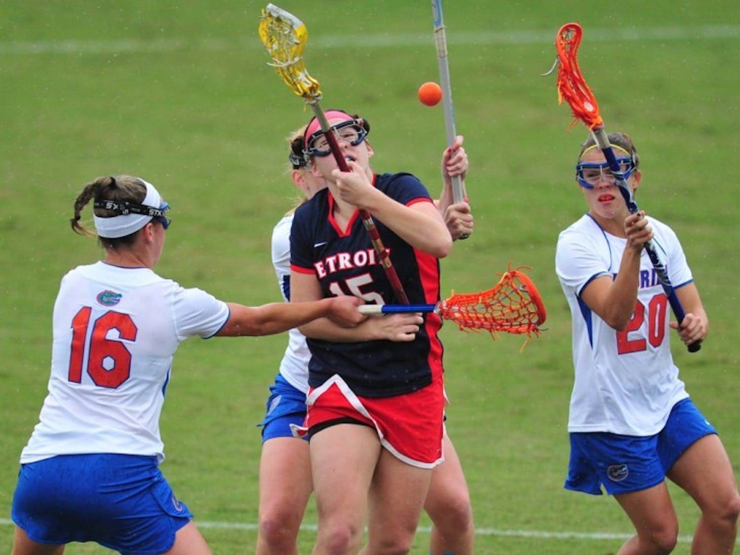 Florida midfielder Nicole Graziano (16) and defender Kayla Stolins (20) attack Detroit midfielder Emily Boissonneault during a 22-3 win on Feb. 26. The Gators are striving for cleaner play as of late.